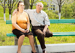 Two adults sitting on a bench.